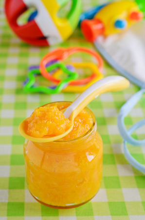 Baby food orange color, resting on a background of children`s toys photo