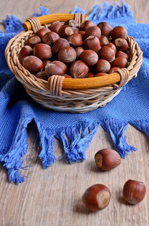 cobnut: Whole fruit hazelnut lie in a wicker basket which is on the blue napkin