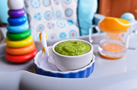 Puree of green in a small bowl stands on a childrens table for feeding photo