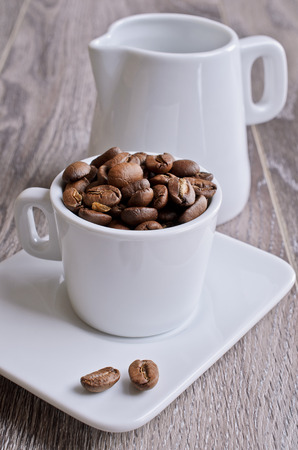 milkman: Small Cup of white filled the large coffee beans on a wooden surface