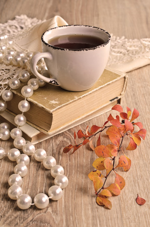 Autumn composition with a Cup, branches, leaves, and old books