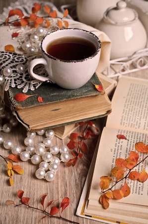 Autumn composition with a Cup, branches, leaves, and old books photo