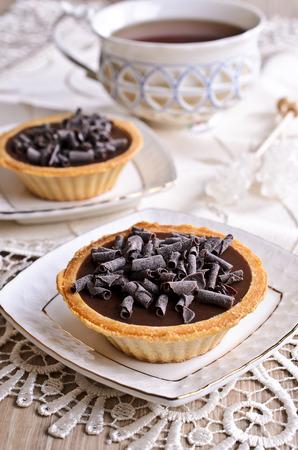 ganache: Tartlet with dark chocolate on a white saucer