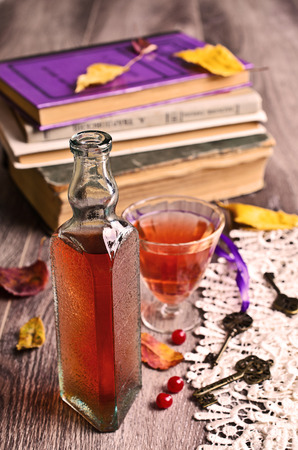 Wine pink color in a small vintage bottle on the background of old books photo