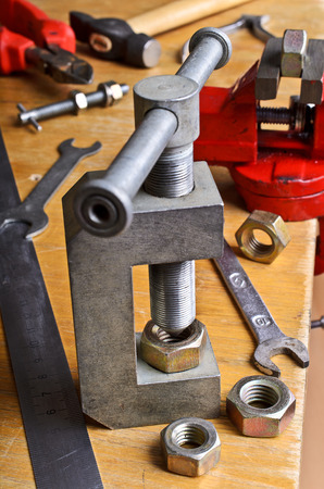 chrome base: Device for threading into the nut by hand, surrounded by instruments on wooden table Stock Photo