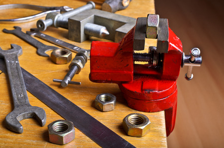 The vise to clamp on a wooden desktop environment tools