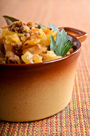portions: Cabbage stewed with meat in the pan portions Stock Photo