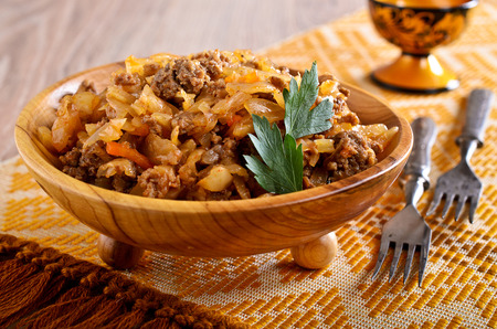 portions: Cabbage stewed with meat in portions wooden plate