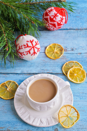 White Cup of hot drink brown color on the background of fir branches photo