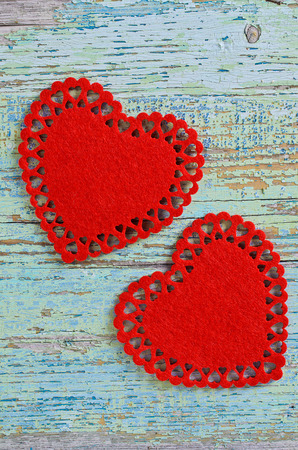 soft tissue: Two red hearts cut from soft tissue are old painted wooden boards