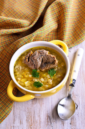 Soup with pearl barley, vegetables and meat in a bowl photo