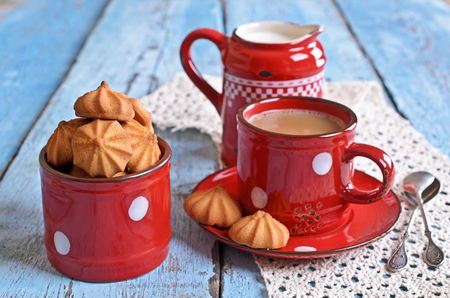 milkman: Small cone-shaped biscuits are brown in ceramic pot of red color on the background of mugs of cocoa and the milkman Stock Photo