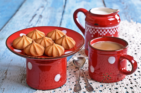 milkman: small cone-shaped biscuits brown on the ceramic support of red on the background of mugs of cocoa and the milkman