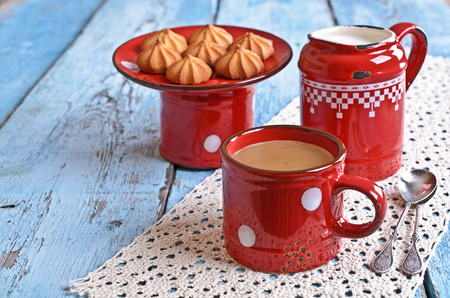 milkman: Drink brown red old ceramic mug against the milkman and biscuits