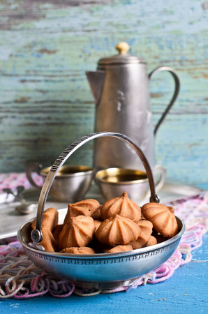 baked treat: small cone-shaped biscuits are brown in metal ware on the background of the coffee pot and cups Stock Photo