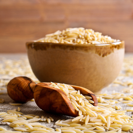 durum: Pasta Orzo in the form of rice grains in a wooden scoop