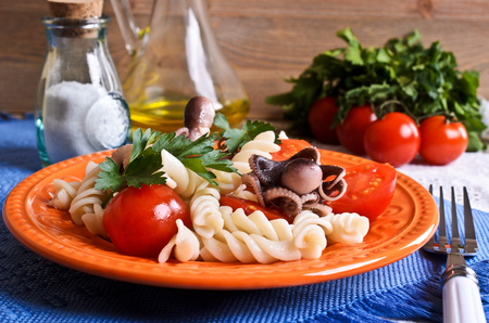 Salad with octopus, pasta and tomato on a ceramic plate photo