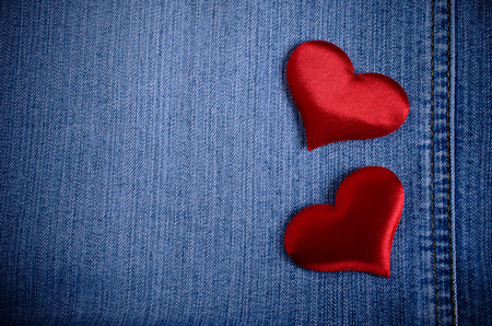 The background for Valentine's Day. Abstraction of denim and hearts of the fabric. Archivio Fotografico