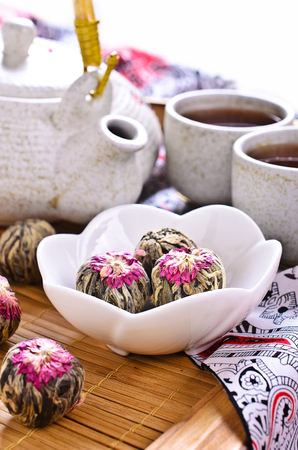 Green tea in the form of a ball with a red flower in a ceramic bowl on a wooden tray surrounded by the kettle and cups made of ceramic photo