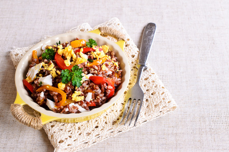 Brown rice with vegetables and eggs in a ceramic bowl