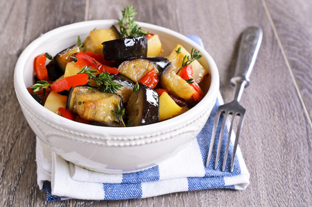 Stew slices of eggplant, peppers and potatoes with branches of thyme on the ceramic plate