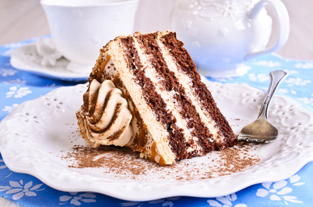 Cut a piece of cake brown with cream on the plate photo
