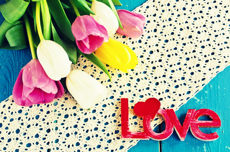 Tulips of different colors and the words love on old wooden boards photo