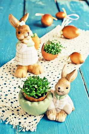 Sprouts green cress in half eggs, painted in gold color, and the Easter Bunny figurine photo