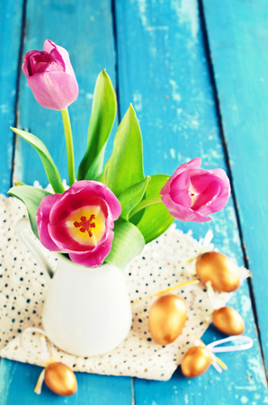 Pink tulips in a vase on the background of the old blue boards and gold Easter eggs photo