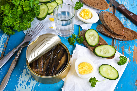 The preserves of sprat in tin Bank on old wooden surface surrounded by other products Banco de Imagens