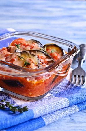 portions: Casserole of eggplant and tomato with cheese in portions glass form