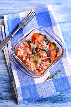 Casserole of eggplant and tomato with cheese in portions glass form photo