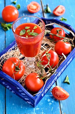 Tomatensaft in einem Glas mit Minze auf dem Hintergrund der Schachtel mit Tomaten auf einem hölzernen Oberfläche Standard-Bild - 38285750