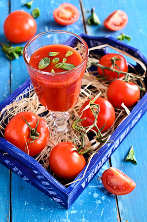 Tomato juice in a glass with mint leaves on the background of the box of tomatoes on a wooden surface Stock Photo