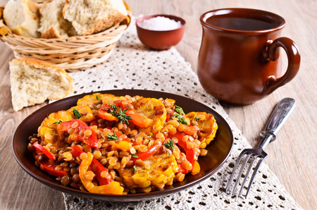 mais: Lentils with paprika and corn in a ceramic plate painted on a wooden surface Stock Photo