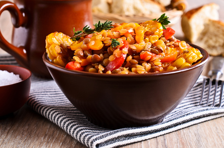 Lentils with paprika and corn in a ceramic plate painted on a wooden surface Stock Photo