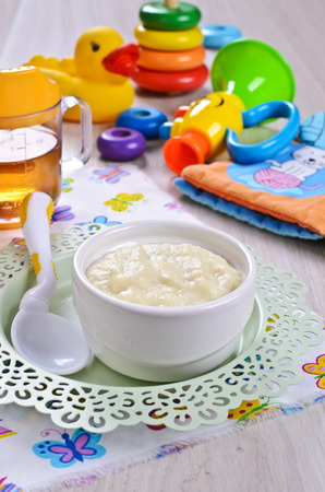 pap: Baby food on the plate on the background of childrens toys Stock Photo