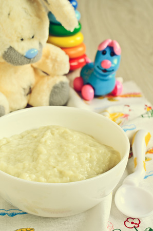 Baby food on the plate on the background of childrens toys photo