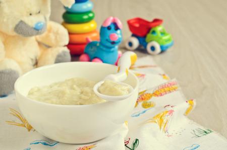 子供のおもちゃの背景にプレートの離乳食