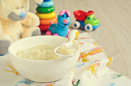 Baby food on the plate on the background of childrens toys Imagens