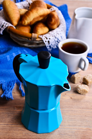 Coffee maker blue color on the background of croissants and utensils for coffee photo