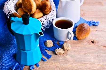 Coffee maker blue color on the background of croissants and utensils for coffee