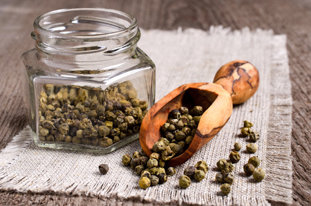 wooden scoop: Green peppercorns in wooden scoop on burlap Stock Photo
