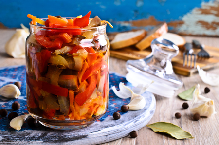 Preserved vegetables in glass jar on wooden background surfaces