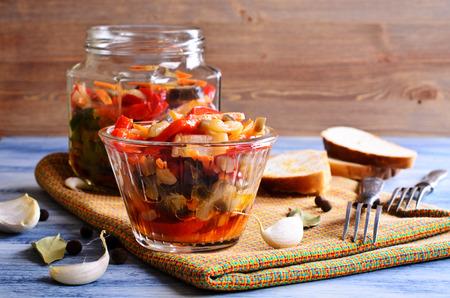 Preserved vegetables in glass jar on wooden background surfaces