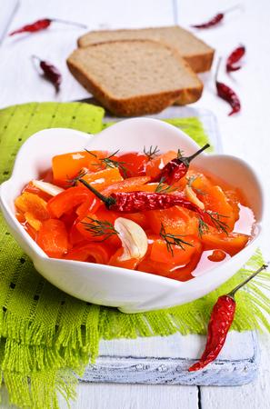 Pepper, sliced, covered in oil in a ceramic dish photo