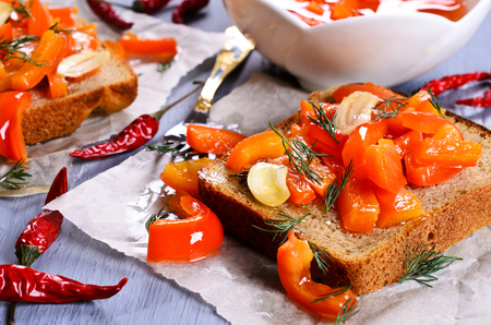 Sandwich with sliced red peppers on parchment photo
