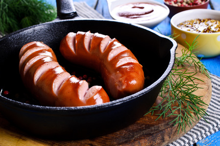 slits: Grilled sausage with slits in a metal pan in rustic style Stock Photo