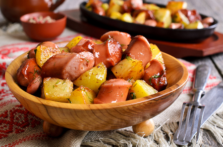 Potatoes with sausages, cut into slices and fried in oil, in rustic style