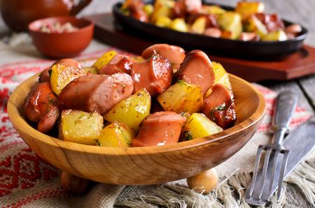 saucisse: Pommes de terre avec des saucisses coup�es en tranches et frits dans l'huile, dans un style rustique